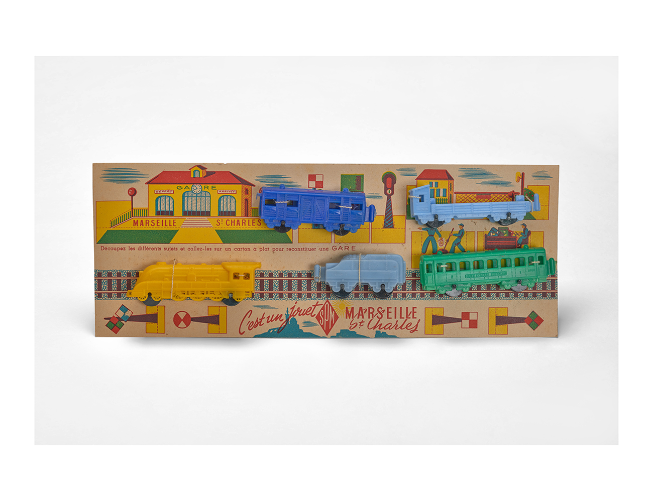 """Marseille St-Charles"" locomotive and its carriages fixed on a cardboard station set, manufactured by SPM, 1950s. Plastic train, cardboard box. Massilia Toy, Marseille © Yves Inchierman"