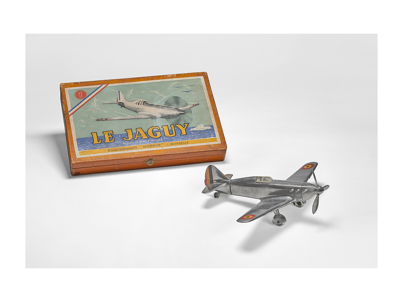 """Le Jaguy"" aircraft and its box, Modalu manufacture, 1947. Cast aluminium aircraft, wooden box. Massilia Toy, Marseille © Yves Inchierman"